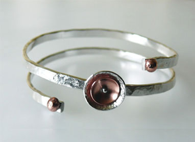 This stunning contemporary sterling silver handcrafted bangle has been made from thick silver wire, forged and formed then complimented with copper.